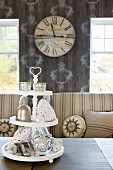Silverware on white cake stand in front of striped sofas with round scatter cushions and nostalgic wall clock