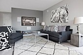 Charcoal sofa set with black and white scatter cushions and rug; flatscreen TV and picture of trees on walls