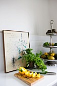 Yellow pepper cut open on wooden chopping board, parsley and cake stand of vegetables in front of old botanical illustration