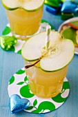 Glasses of apple juice topped with slices of apples as straw holders