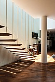 Pattern of light and shade cast by airy, floating stair treads attached to baluster rods below mezzanine level