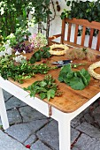 Secateurs, freshly cut flowers, twigs and straw wreaths on garden table