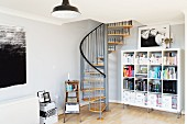 Corner of living room with bookcase and spiral staircase leading to mezzanine in English loft apartment in converted factory