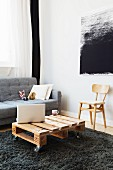 Wooden palette used as coffee table in front of sofa and black and white textile artwork on wall