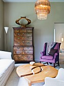 Eclectic style, living room with designer coffee table, antique armoire and armchair upholstered in purple