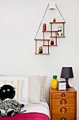 Jugendbett mit schwarzweisser Kuschelpuppe und Retro Holzkommode; an der Wand eine Art minimalistischer Setzkasten mit Figürchen
