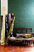Bolts of patterned fabrics and wooden bench against brick wall painted petrol blue