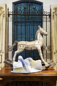 Old rocking horse and patchwork blanket on antique table in front of wrought iron window grille