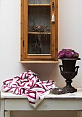 Knitted blanket with graphic pattern and roses in urn on vintage table below glass-fronted cabinet