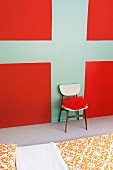 Red fabric on chair against wall painted with graphic design in red and turquoise beyond bed with ornamental patterned bed linen