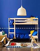 Blaues Kinderzimmer für zwei - mit Hochbett aus Naturholz, Korblampe und Holzspielzeug auf Webteppich