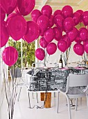 Chairs painted pale grey around table decorated with hot pink balloons