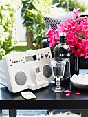 Stereo system and iPod next to liqueur glass and bottle of vodka in front of pink bouquet on black side table
