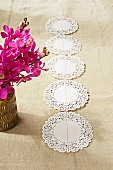 Row of doilies on linen fabric next to pink potted orchid