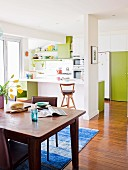 Open-plan, white kitchen with green door elements and dark wooden dining table