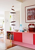 Sideboard painted pink and red with books in open cupboard below wooden mobile