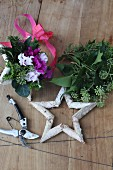 Hand-crafted birch bark stars decorated with cyclamen and leaves and secateurs on wooden surface
