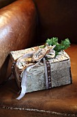 Small festive parcel decorated with birch bark and ribbon on leather armchair