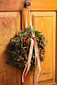 Festive wreath with berries and ribbons hung on cupboard door