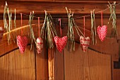 Garland of red fabric love-hearts and pine needles hung on cupboard