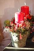 Rustic Christmas arrangement of twigs and candles in plant pots
