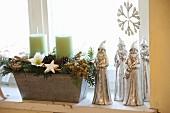 Rustikale Kerzendeko neben silbernen Weihnachtsmännern