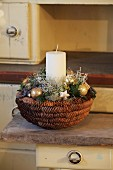 Festive arrangement with candle in basket made from pine cones