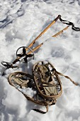 Vintage snow shoes and ski poles lying in snow