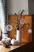 White, crocheted stars hanging from gnarled branch and bundt cake on wood-panelled cabin windowsill