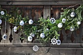 Rustic wooden balustrade of mountain hut balcony decorated with fir branches, crocheted stars and knitted baubles
