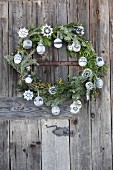 Christmas wreath of fir branches with crocheted stars and knitted baubles hanging on rustic wooden door
