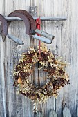Autumnal wreath with berries under rusty sickles hanging from wooden pole