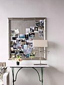 Collection of souvenir photos on pin board in silver frame