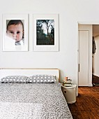 White and grey patterned bedspread and pillows on double bed below photos on wall; open door to one side with view into hall