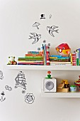 Detail of children's books and toys on white floating shelves with various decorative stickers on wall
