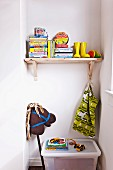Books and yellow Wellingtons on wooden shelf in niche with hobby horse and toy box on floor