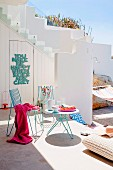 Terrace of white, Mediterranean house with metal table & chairs, floor cushions & hammock