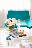 Crystal candlestick on tray table in front of turquoise lounge chair