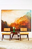 Designer wooden chairs with seat cushions an vase of flowers on side table in front of landscape painting
