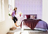 Sunny bedroom with bed linen and graphic wallpaper in various shades of purple