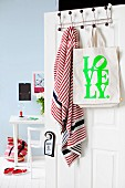Printed cloth bag and scarf hanging on hooks with black knobs on open door and view of desk against wall painted pale blue