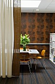 Bauhaus chairs at white table on striped rug, bronze wallpaper with dark floral pattern and floor-length curtains to one side