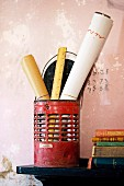Rolls of paper and rulers in old, red metal container next to stack of books on bracket mounted on wall with peeling pink paint