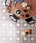 Round dining table and chairs on tiled floor with decorative graphic pattern in black, white & grey