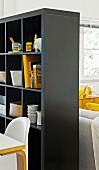 Schwarzes Regal als Raumteiler mit Stauraum für Geschirr und Bücher zwischen Essplatz und Loungebereich
