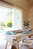 Wood-clad dining room with view of pool - pale wooden table, rustic wooden bowl and white plastic shell chairs