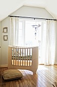 Custom-made, pale wood cot in front of balcony doors with airy curtains in attic nursery