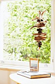 Gnarled pieces of wood threaded and hung in window above book and framed photo on side table