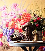 Small bust and bouquet on round table in front of floral wall hanging