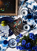 Floral fan, bowls and potted cornflowers on blue and white patterned tablecloth